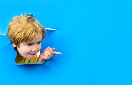 Curious child looks through hole paper. Boy peeking from ripped paper hole. Surprised kid points on copy space. Blonde small toddler shows finger on copy space. Sale, discount, season sales. Advertise