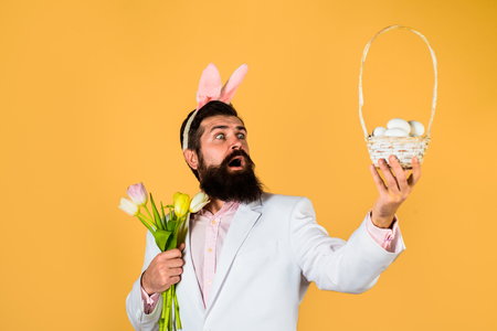 Happy Easter. Surprised bearded man in suit holds basket with eggs. Rabbit man in bunny mask with flower. Happy Easter. Preparation for Easter. Spring holiday. Spring flower. Easter bunny costume.