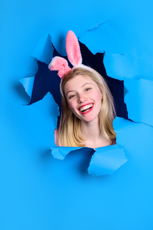 Easter Day. Through paper. Happy easter! Woman with bunny ears. Smiling woman looking through paper. Egg hunt. Easter. Bunny. Easter hunt. Bunny ears. Breaking paper. Sale. Discount. Stockfoto