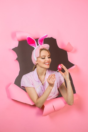 Happy easter! Painting eggs. Woman painting egg. White bunny. Bunny ears. Through paper. Shop Online for easter decoration. Breaking paper. Sale. Discount.