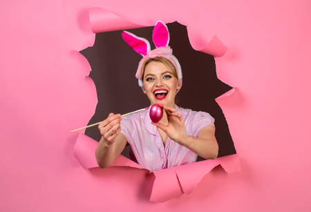 Happy easter! Through paper. Hunts for Easter eggs. Woman with fake bunny ears. Happy woman painting easter egg. Egg hunt. Easter. Bunny. Easter hunt. Fake bunny ears. Breaking paper. Sale. Discount.
