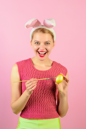 Festive bunny&eggs season. Happy young woman in bunny ears. Easter, holidays, tradition, people concept - woman coloring easter egg. Girl painting easter eggs. Pretty girl preparing for Easter. Stock Photo
