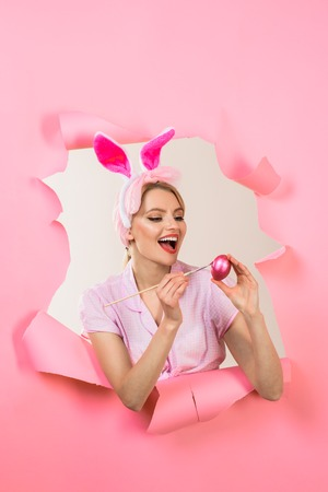 Easter Day. Painting eggs for Easter. Smiling woman peeks through paper. Pin up girl with bunny ears. Woman breaks paper. Through paper. Happy easter! Happy woman painting egg.