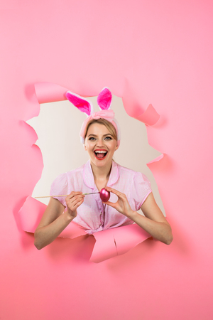 Easter Day. Pin up woman peeks through paper. Pin up girl with bunny ears. Woman breaks paper. Through paper. Happy easter! Smiling woman painting egg. Painting eggs for Easter.