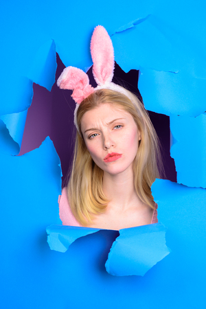 Happy easter! Through paper. Easter Day. Woman with bunny ears. Blonde woman looking through paper . Egg hunt. Easter. Bunny. Easter hunt. Bunny ears. Breaking paper. Spring holidays. White rabbit. Stockfoto