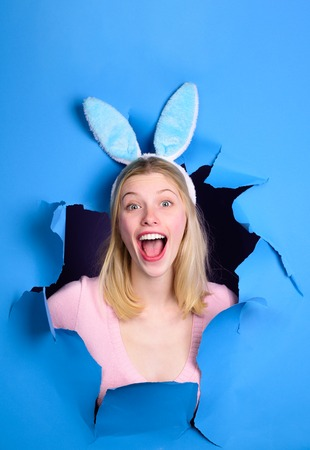 Happy easter! Through paper. Easter Day. Woman with fake bunny ears. Happy woman looking through paper . Egg hunt. Easter. Bunny. Easter hunt. Fake bunny ears. Breaking paper. Sale. Discount.