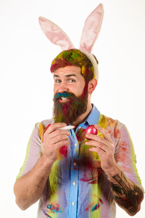 Bearded man painting egg. Easter egg ideas. Painting. Season Sale. Discount. Bearded man with bunny ears painting egg. Spring holidays. Spring holidays.