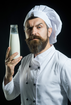 Chef with milk, milkshake or yogurt. Healthy food, organic ingredients, protein diet concept - cook with proud face in white uniform presents bottle of milk. Ideal dairy solution. 写真素材