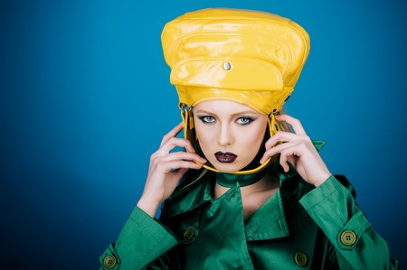Shopping, discount, sale, style concept - fashionable woman with perfect makeup in green jacket with female bag on head. Lady in green coat hold stylish fashion yellow handbag behind strap. Copy space