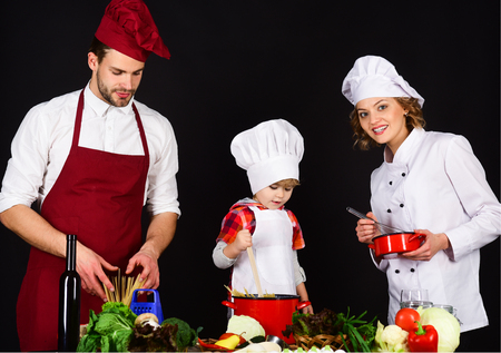 Cheerful parents teaching son how to cook. Homemade food. Preparation to dinner. Concept of friendly family. Parents with child preparing dinner.