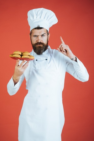 Handsome chef holds plate with cookies. Man with beard and mustache holds plate of oatmeal cookies. Bearded chef shows finger up. Handsome bearded man cook chef in white uniform.
