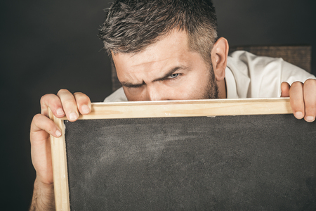 Cropped photo of mans head with eyes looking at camera. Man holds black board, ready for your text, advertising or slogan. Man holding a chalk board. Bearded man hiding behind a black board for your  写真素材