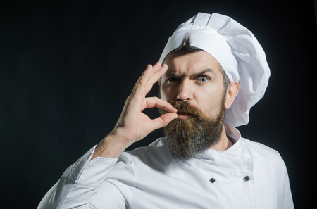 Chef, cook making tasty delicious gesture by kissing fingers. Confident bearded male chef in white uniform with perfect sign. Master chef, cook or baker giving sign of good taste with hand. Copy space