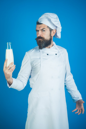 Man with beard and mustache in white uniform holds glass bottle dairy product on blue background. Homemade kitchen, restaurant dairy meal, cooking concept - chef with bottle milkshake, kefir, yogurt.