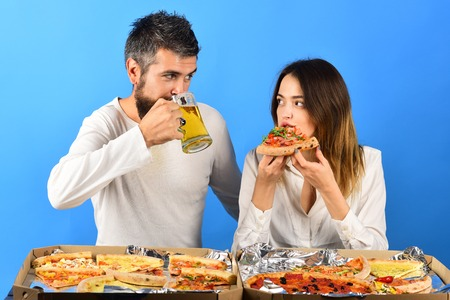 Pizza time. Romantic couple eating pizza. Dating, consumerism, food, lifestyle concept - beautiful loving couple in casual clothes enjoy pizza. Man drinks beer, woman eating pizza. Fast food. Isolated Archivio Fotografico