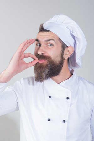 Chef in white uniform shows hand sign for perfection and excellence. Professional chef man showing perfect sign. Profession, cooking, gesture and food concept - happy male chef shows delicious gesture 写真素材