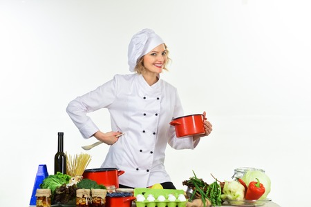 Female chef holds pan with food. Cooking and professional culinary concept. Food preparation concept. Cooking, grits, organic food, dieting, healthy food cooking, restaurant concept.