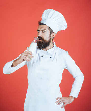 Dairy. Bearded male chef drinking bottle of milk. Organic ingredients concept. Cook in white uniform has liter of fresh milk, milkshake, yogurt. Man with beard, mustache holds glass bottle. Copy space 写真素材