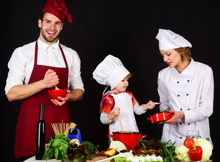 Happy family in kitchen. Healthy food at home. Adorable kid in chef hat. Preparation to dinner. Parents with child preparing dinner. Cheerful parents teaching a boy how to cook. Homemade food.