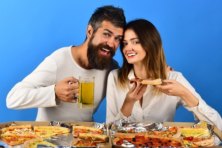 Pizza time. Fast food. Man drinks beer, woman eating pizza. Romantic couple eating pizza. Dating, consumerism, food, lifestyle concept - beautiful loving couple in casual clothes enjoy pizza. Isolated Stock fotó