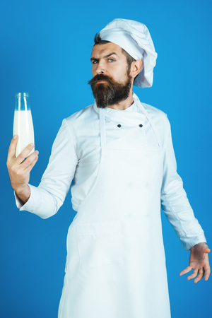 Preparation meal from fresh ingredients, cooking process concept - chef having glass bottle fresh milk. Male in white cooking clothes hold bottle dairy product. Chef hold glass bottle of kefir, yogurt