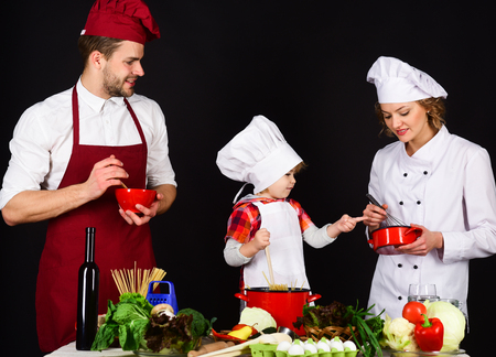 Happy loving family preparing dinner together. Child with parents at kitchen table cooking. Homemade food. Cute little boy and his parents smiling while cooking. Concept of friendly family.