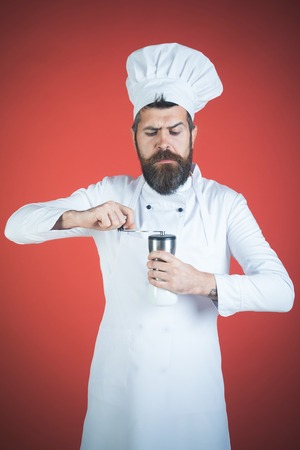 Adding seasoning. Bearded male chef holds salt shaker. Bearded man. Food, cooking, preparation concept. Professional food preparation concept. 写真素材
