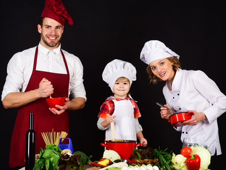Concept of friendly family. Happy family in kitchen. Healthy food at home. Adorable smiling kid in chef hat with parents. Cooking together. Preparation to breakfast, dinner, supper.