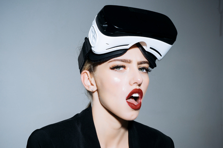 Amazed attractive girl with VR device. Woman in VR headset. Virtual reality goggles. Connection, future technology, progress concept - excited surprised woman using 3d goggles watching virtual reality Stockfoto