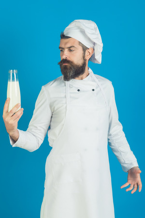 Professional chef in white uniform. Head-cook holds bottle fresh farmer milk. Bearded baker or confectioner looking to bottle of milk. Cooking process concept. Preparation meal from fresh ingredients.
