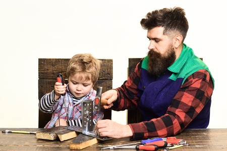 Concept of repair&assistance - concentrated cute little boy learning to use tools with dad. Father&son repairing together. Fatherhood concept - kid with screwdriver, parent with hammer work together.