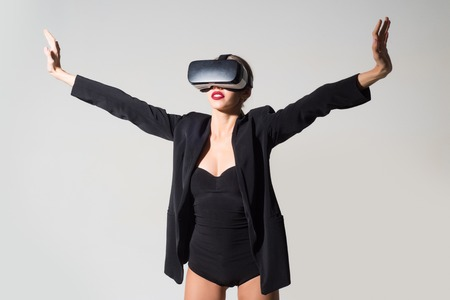 Future technology, connection, new generation, progress concept. Woman using VR headset. Virtual reality glasses, entertainment. Emotional woman wearing virtual reality goggles, gesturing with hands.