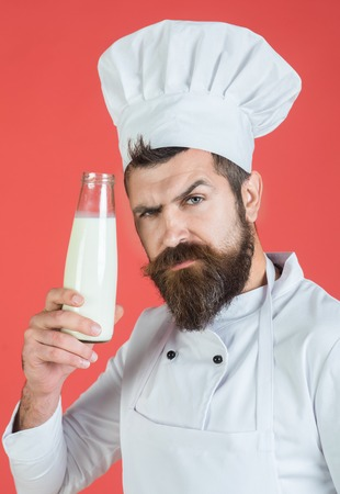 Dairy products and cooking concept. Protein diet concept. Serious chef with glass bottle milkshake or yogurt. Ideal dairy solution. Bearded male cook holding bottle of milk. Chef using dairy products.