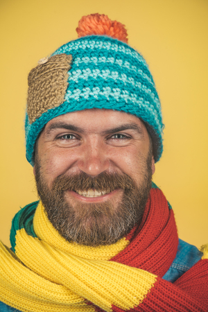 Closeup portrait attractive bearded man in warm knitted hat, scarf. Health, beauty and people concept - portrait of smiling caucasian man with beard in fashionable scarf and hat. Male winter fashion.