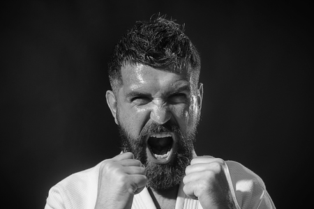Screaming handsome male mixed martial arts fighter. Strong muscular fit fitness model shows competition strength. Caucasian male model in kimono staring angry. Karate bearded man in action.Black&white