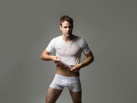 Silny wysportowany mężczyzna w bieliźnie. Seksowny przystojny mężczyzna w mokrej koszulce. Zmysłowy mężczyzna w bieliźnie. Muskularny model mężczyzna w białej bieliźnie. Stroje kąpielowe i bielizna męska. Mężczyzna w bokserkach. Moda. Zdjęcie Seryjne
