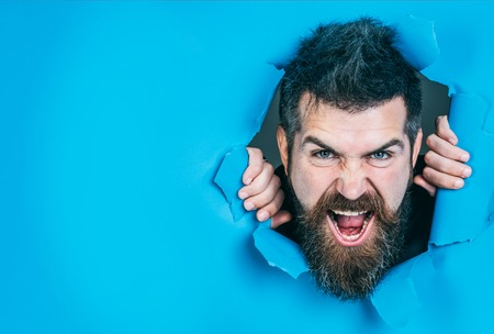 Bearded man making hole in paper. View of angry male face through hole in blue paper. Angry man looking through hole. Bearded man in paper. Isolated. Close up. Emotions. Imagens