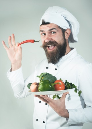 Male chef in cook uniform holds pepper in hand. Food service. Organic food. Healthy diet. Professional culinary concept. ?hef in white uniform holds plate with vegetables. Green grocery concept. Reklamní fotografie