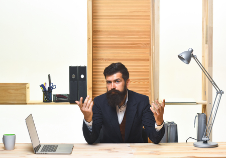 Confused businessman. Office worker. Portrait of bearded businessman. Serious businessman in suit. Man sitting at table. Handsome bearded office worker. Office.