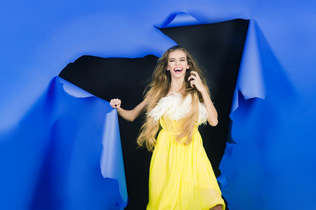 Smiling girl break through hole in blue paper. Beautiful girl in yellow dress passes through hole in paper. Trendy clothes. Fashion products. Summer sale. Sales. Discount. Makeup products.