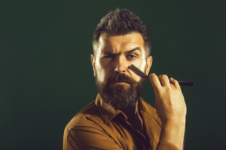 Barbershop ads concept. Bearded barber with straight razor near beard. Barbershop equipment. Hipster man having shave with razor blade. Hairdresser demonstrating sharp blade of barbershop accessory.