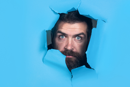 Bearded man making hole in paper. View of scared man through hole in blue paper. Scared man peeking through hole. Bearded man making hole in paper. Isolated. Close up. Emotions.
