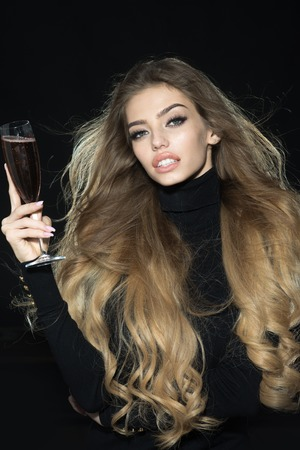 Blonde girl with gorgeous hair holds glass of champagne. Professional makeup. Seductive girl with long hair in black golf with glass of wine. Romantic woman with healthy hair with glass of champagne. Zdjęcie Seryjne