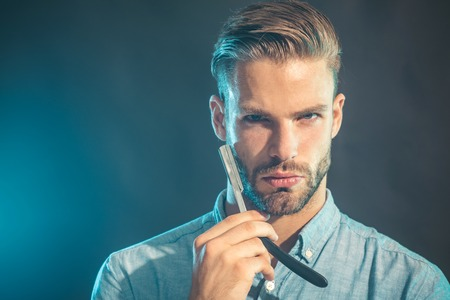 Handsome bearded man with straight razor. Hipster man with beard and mustache holds razor in his hand. Fashion and beauty. Barber, barbershop and hairdresser. Barbershop service concept. Copy space.