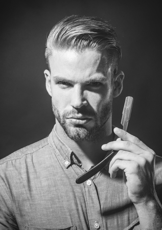 Barber with stylish haircut holds barbershop accessory. Serious man with beardμstache with dangerous razor. Vintage tools for barbers. Professional barber holds straight razor near face. Black&white