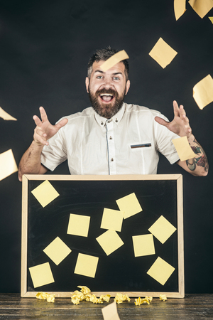Cheerful businessman standing at table with blackboard with reminder stickers. Attractive joyful businessman throws up stickers. Business, employment, brainstorming concept - blackboard with notes.