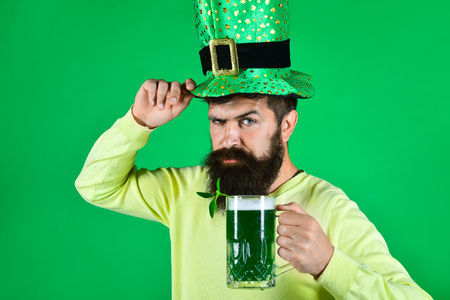St. Patrick's Day. Bearded man in leprechaun hat. Portrait of pensive man with green beer. Bearded leprechaun. Happy Irish leprechaun with black beard. Bearded man. Green background. Irish tradition. Stock Photo - 124983774