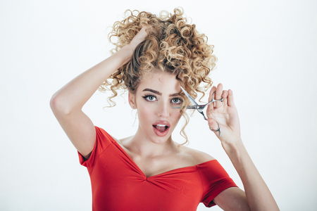 Surprised girl with curly hair holds scissors. Hairdresser. Beauty industry profession. Makeup and cosmetics for skin care. Beauty and style. Isolated on white background.