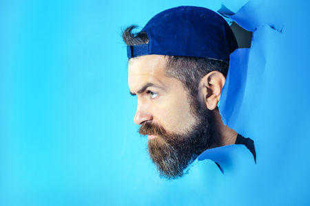Serious man in cap looking through hole in blue paper. Bearded man making hole in paper. Man gazing from hole in wall. Hole in paper with serious man looking through. Copy space for advertising. Imagens
