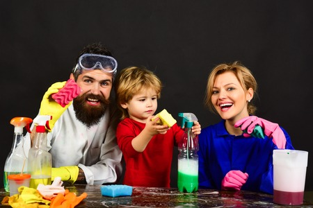 Cleaning concept. Family sit at wooden table with cleaning products. Smiling bearded man holds sponge. Woman holds spray. Cleaning activities concept. Cute little helper. Isolated on black background. Banco de Imagens